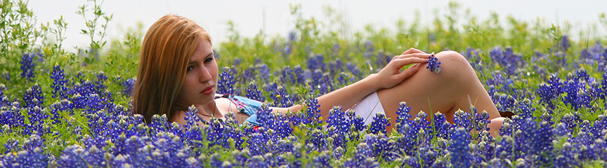 Girl get her picture taken with Bluebonnets in Brenham Texas.
